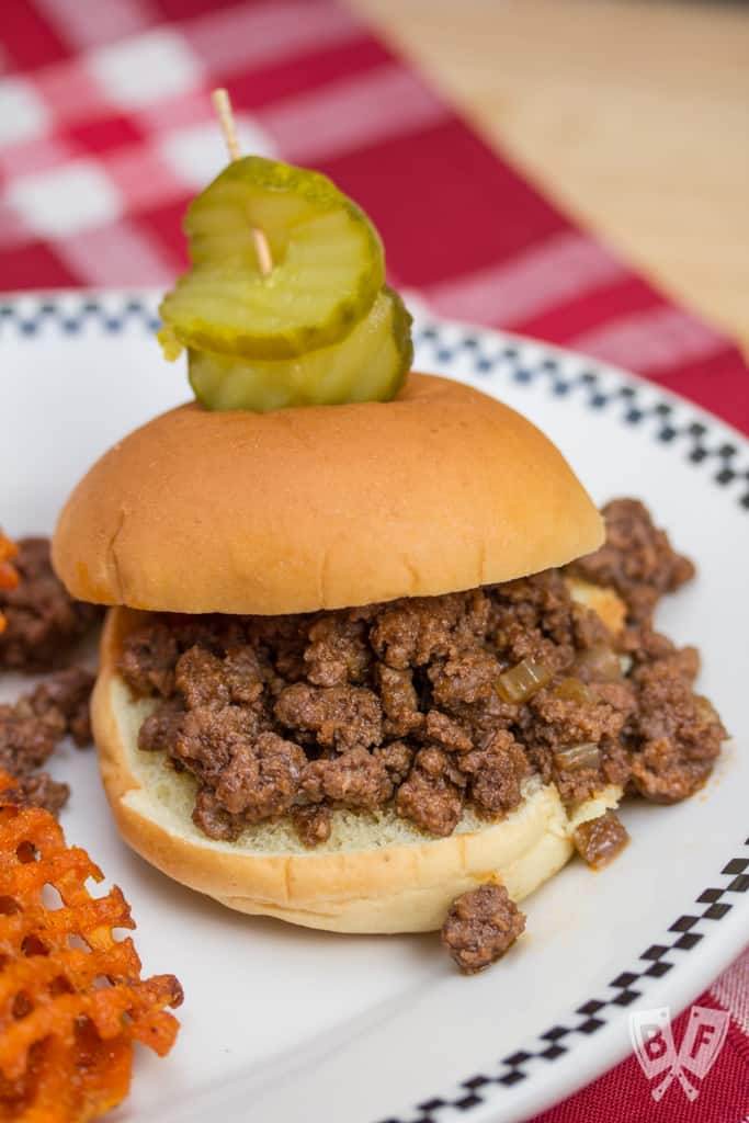 Sloppy joe on a plate with pickles