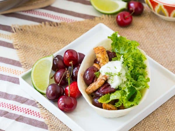 Cherry chicken taco boat on a white plate with fresh cherries