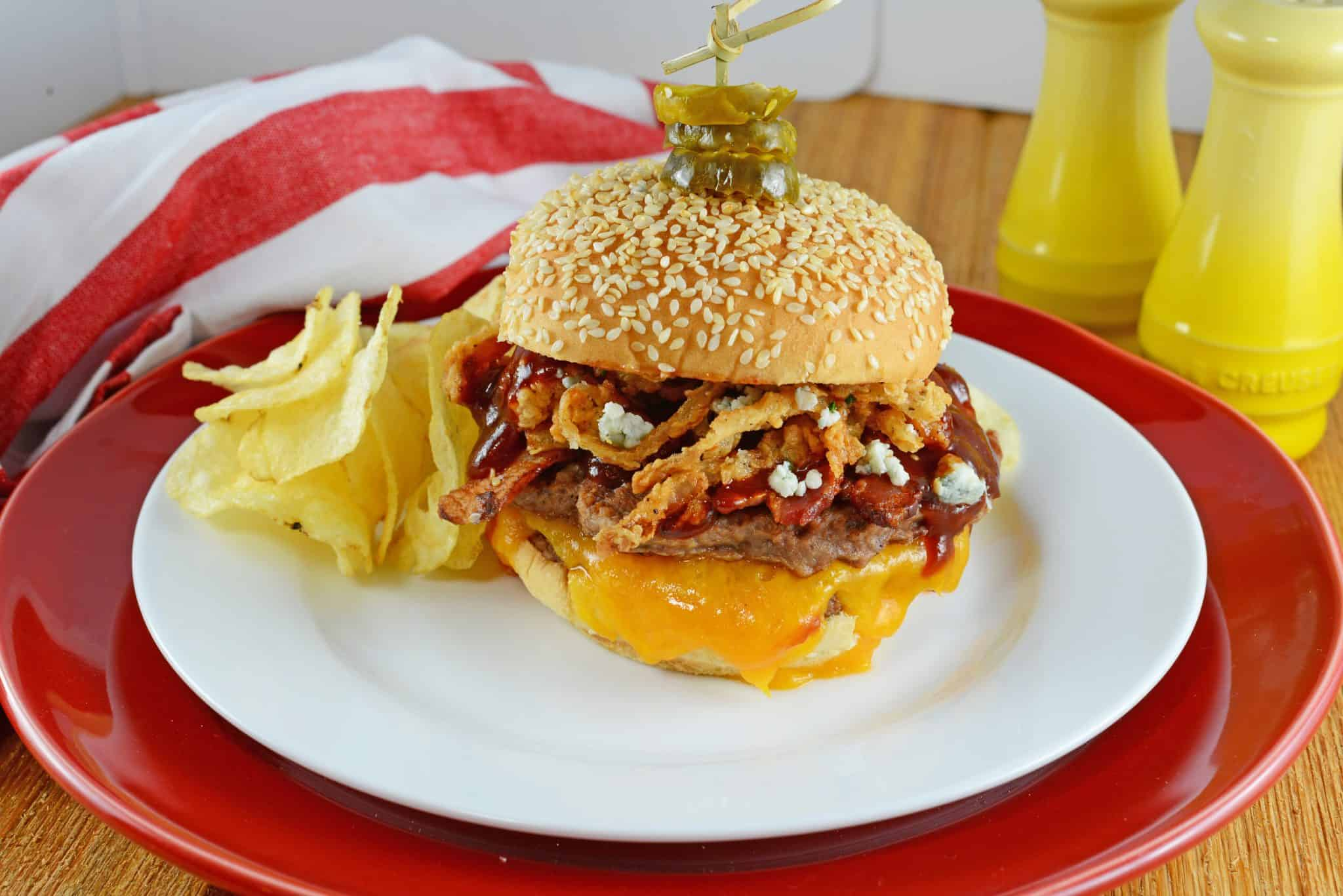 Cowboy burger with chips on a white plate