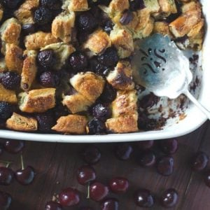 Dark chocolate cherry bread pudding in a white baking dish