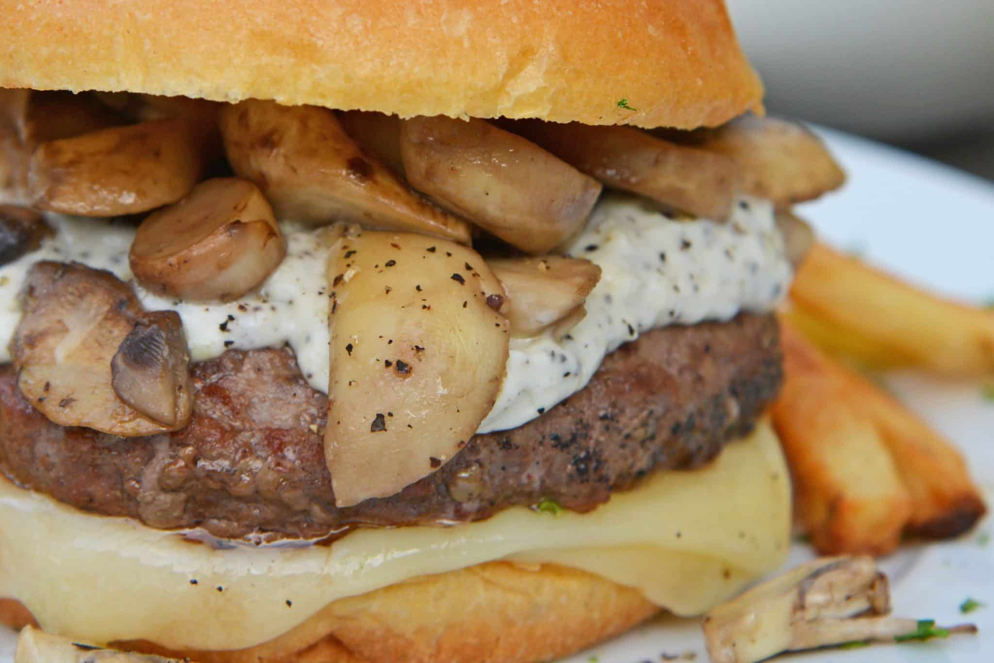 A Garlic Truffle Burger is the perfect way to make a gourmet burger at home. Truffle Aioli, sautéed mushrooms, Swiss cheese and a juicy burger patty on a buttery brioche roll. #gourmetburgers #truffleburgers www.savoryexperiments.com