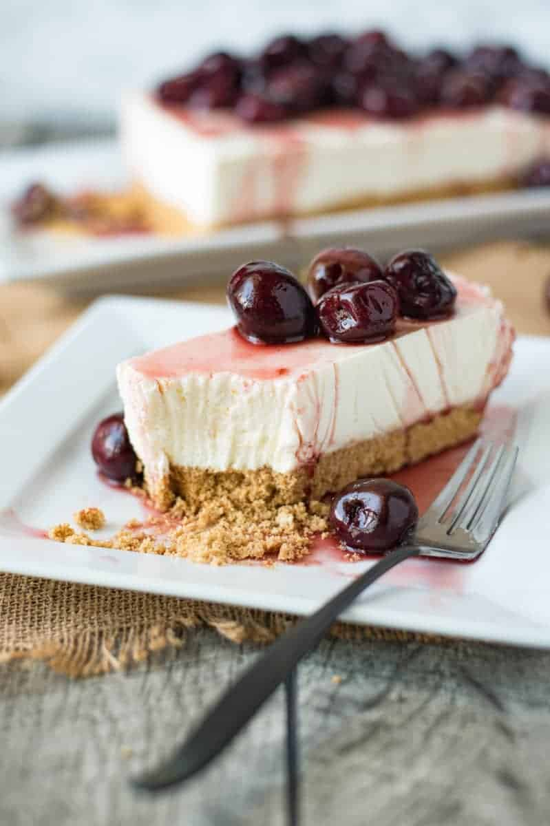A slice of cherry lemon cheesecake on a white plate