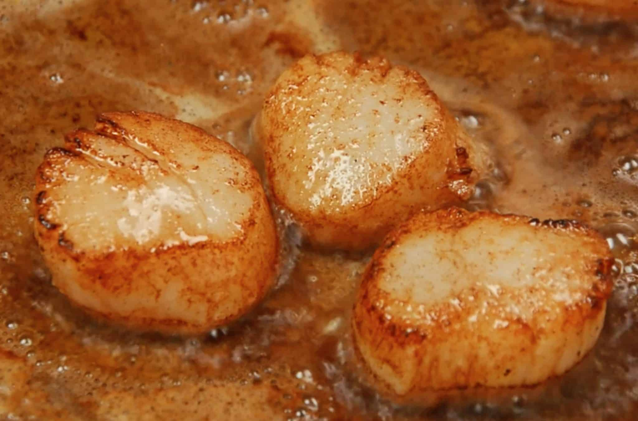 Pan Seared Scallops at home are easy to make. Learn how to prevent your scallops from sticking and get restaurant quality crust every time! #howtosearscallops #howtocookscallops www.savoryexperiments.com