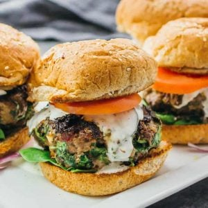 Four greek burger on a white platter