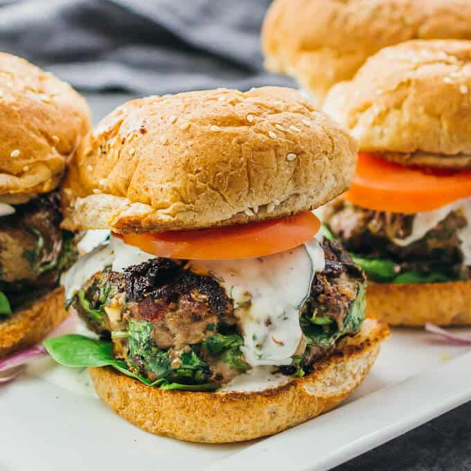 Four greek burger on a white platter