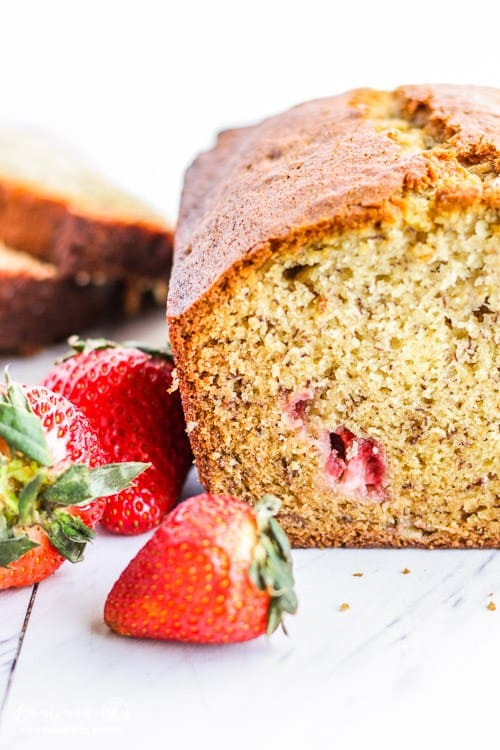 A loaf of strawberry banana bread with strawberries