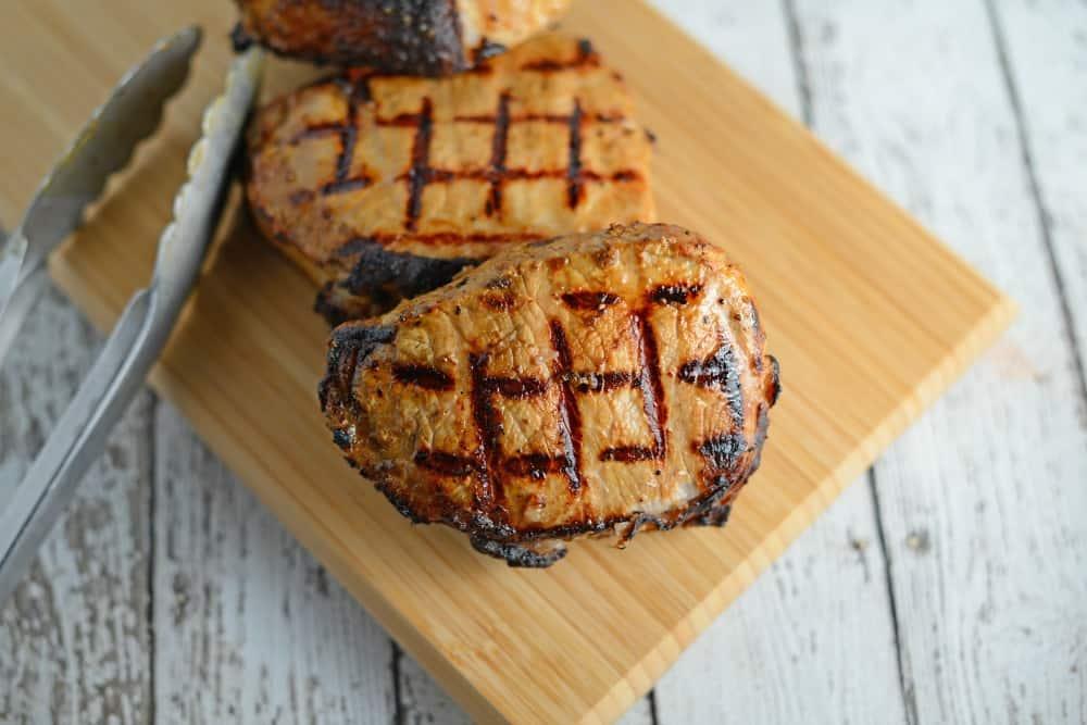 Two dijon pork chops on a cutting board