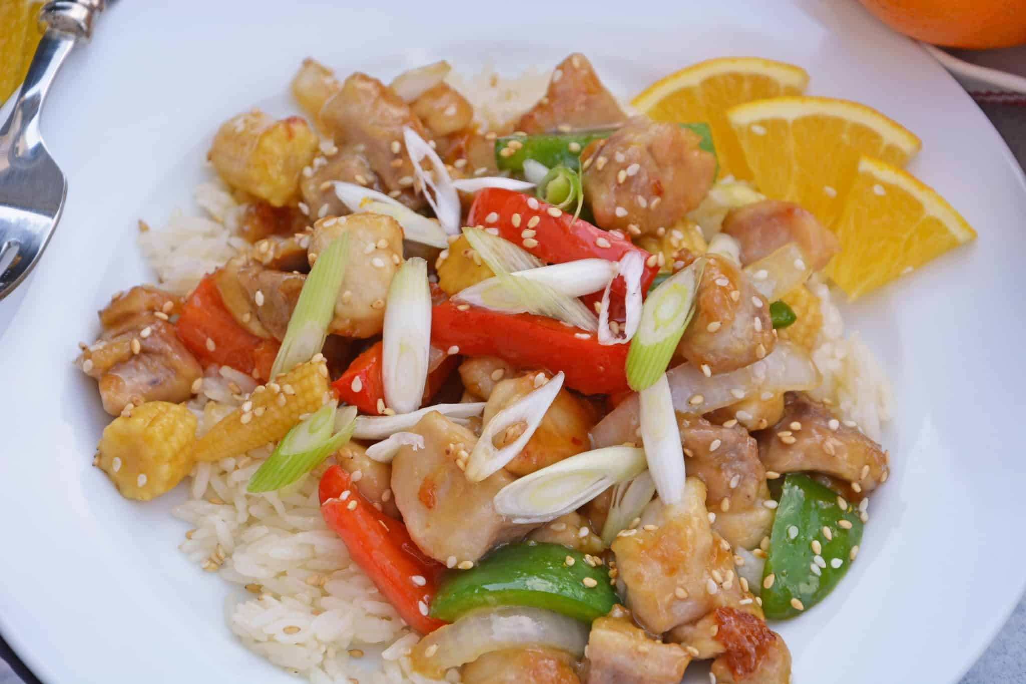 This Orange Chicken Recipe is amped up with bell pepper, baby corn and carrots in a delicious savory orange sauce over rice. Garnish with scallions sesame seeds and orange zest for the best homemade Chinese food. #homemadeorangechicken #orangechickenrecipe www.savoryexperiments.com