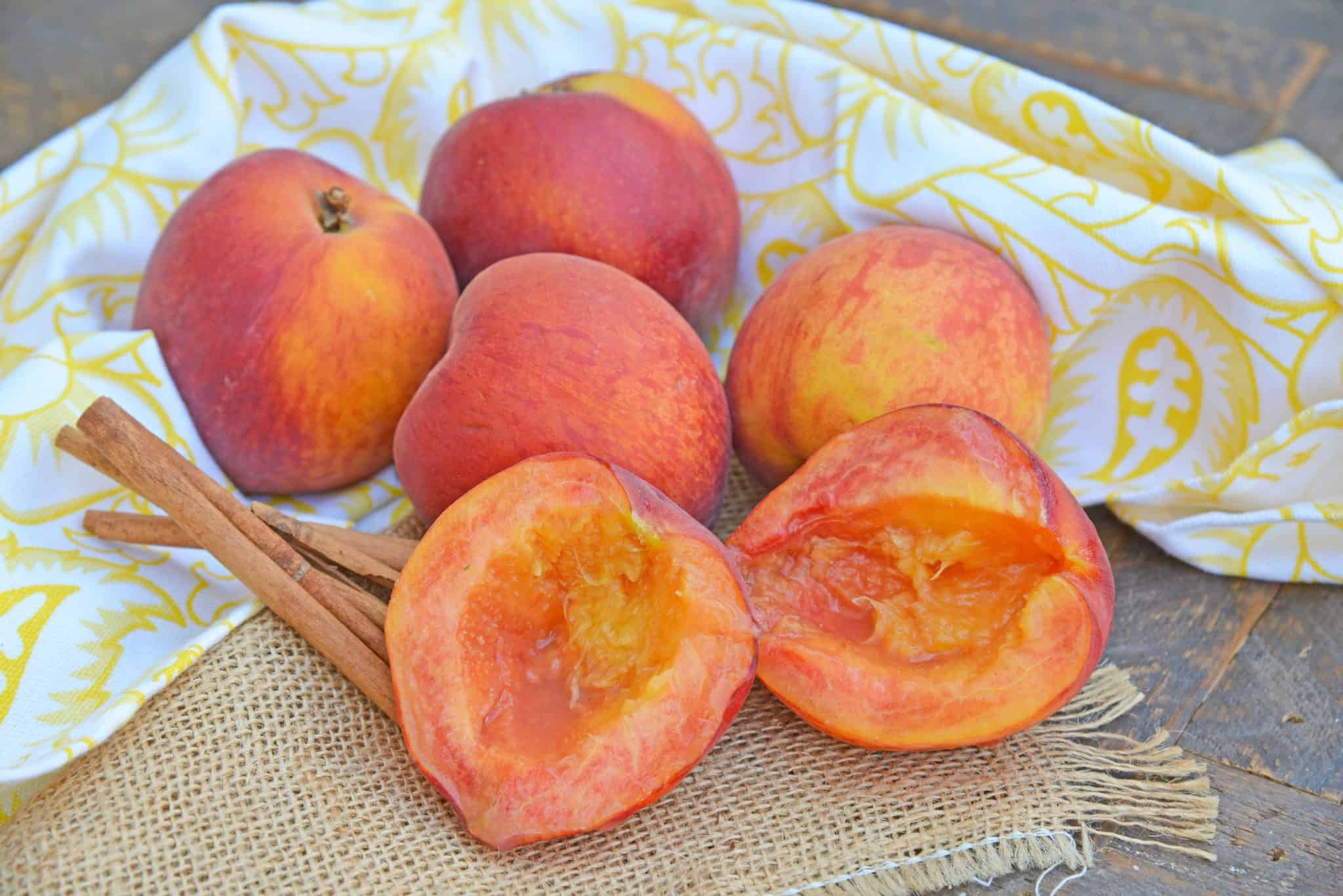 Grilled Peaches basted with cinnamon brown sugar and butter are the ultimate summer dessert idea. Add vanilla ice cream and fresh raspberries for dessert perfection! #grilledpeaches www.savoryexperiments.com