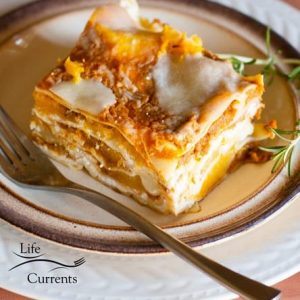 A slice of pumpkin lasagna on a plate with a fork