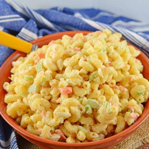 Classic macaroni salad in an orange bowl with a yellow spoon