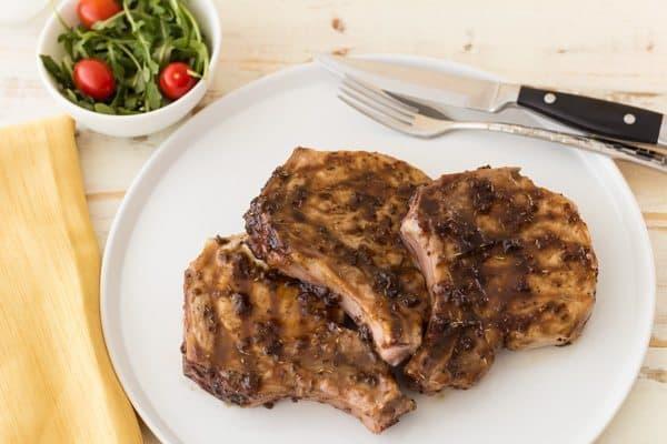 Three jalapeno raspberry pork chops on a white plate