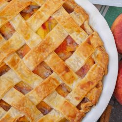 Peach pie in a pie plate with peaches