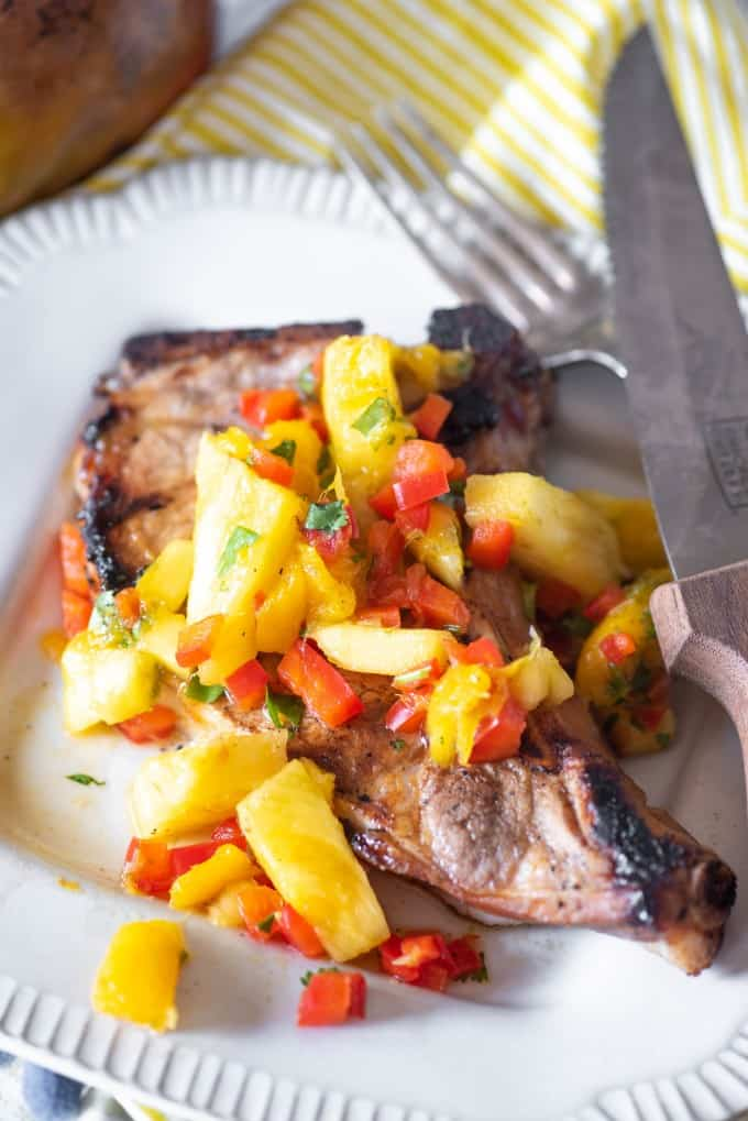 Tropical pork chop on a white plate with a fork and knife