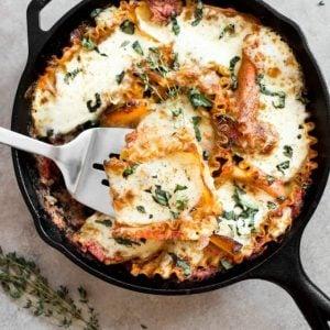 Lasagna in a skillet with a spatula