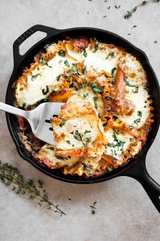 Lasagna in a skillet with a spatula