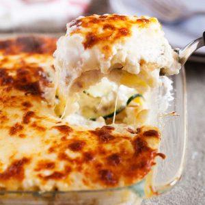 A slice of garlic white lasagna on a spatula