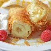 Banana fried cheesecake cut in half with raspberries
