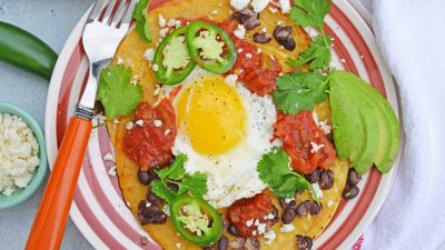 Huevos Rancheros are a great way to spice up your breakfast. Lacey eggs with a runny yolk over warm corn tortillas, chunky salsa, black beans, cilantro and queso fresco. #huevosrancheros www.savoryexperiments.com