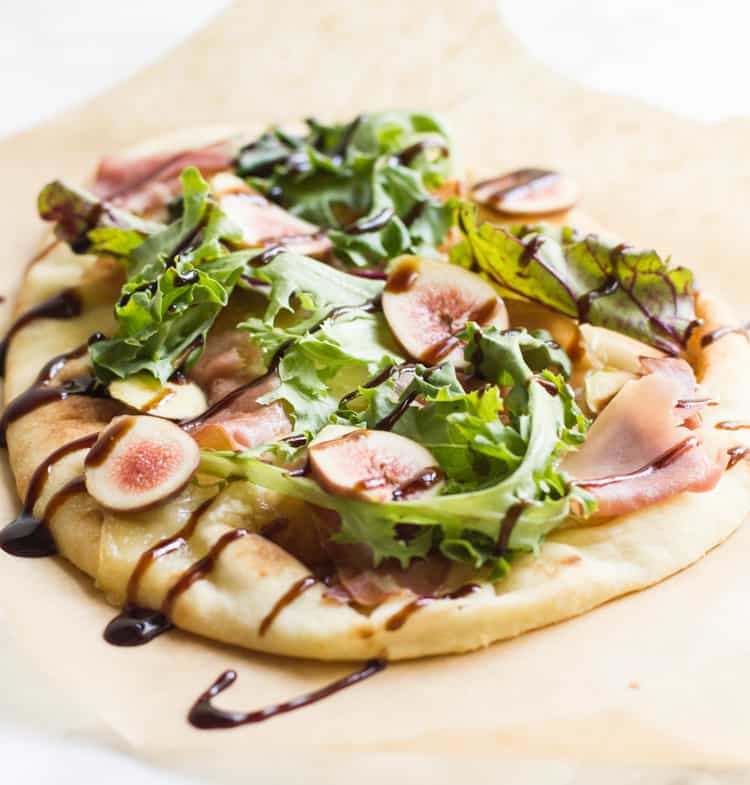 Brie fig and prosciutto pizza on parchment paper