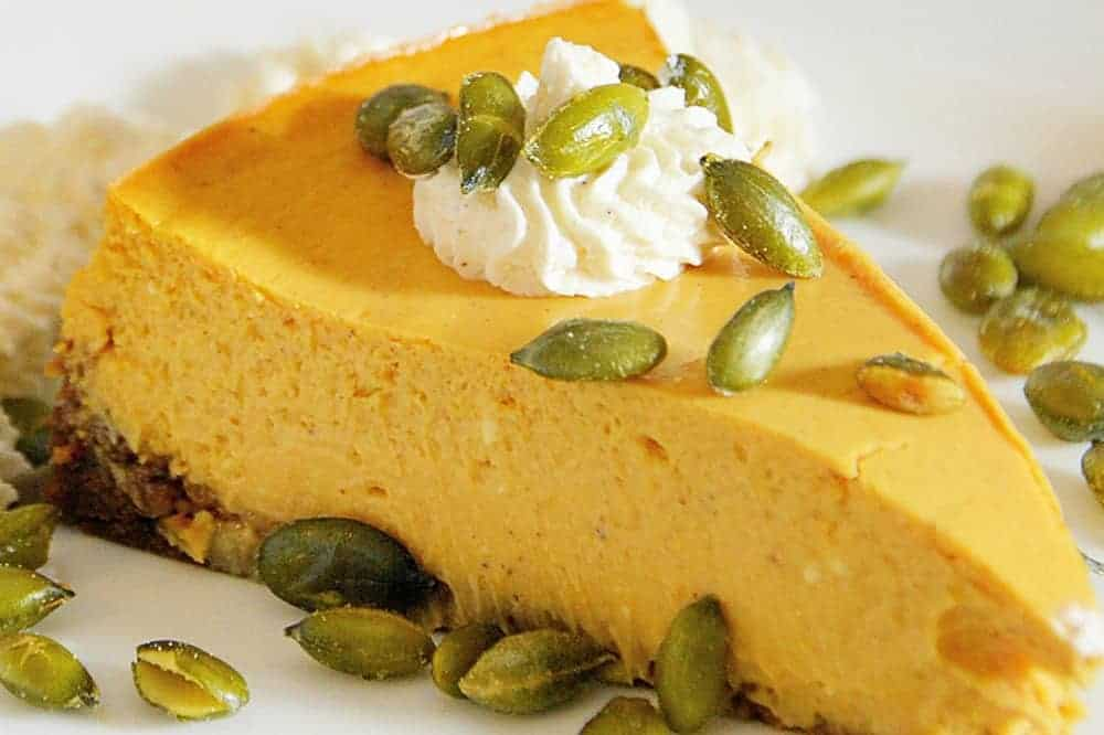 Slice of pumpkin cheesecake topped with pumpkin seeds
