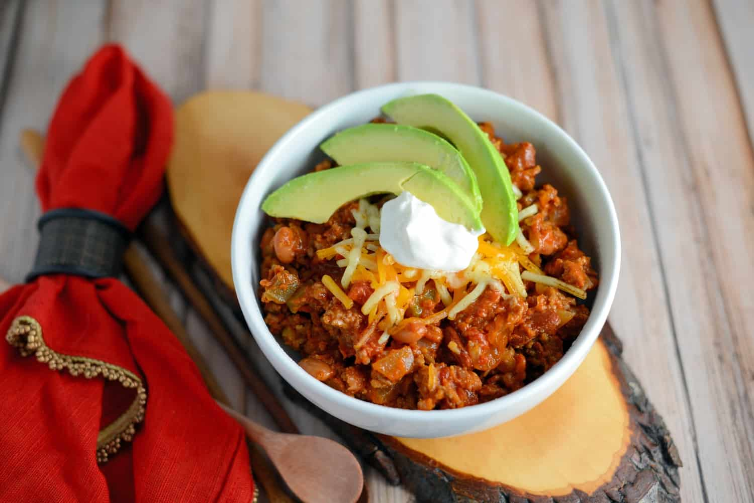 Quick chili in a white bowl topped with sour cream and avocado