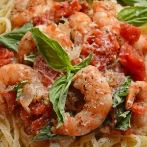 Tomato Basil Shrimp Pasta is an easy and healthy shrimp pasta recipe. It's great for busy weeknights but full of flavor and sure to impress guests! #shrimppasta #shrimpmeals #shrimppastarecipe www.savoryexperiments.com