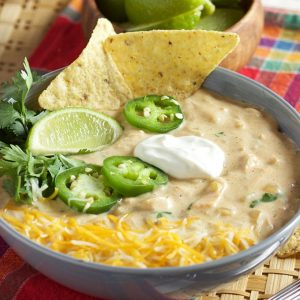 White chicken chili in a blue bowl with tortilla chips
