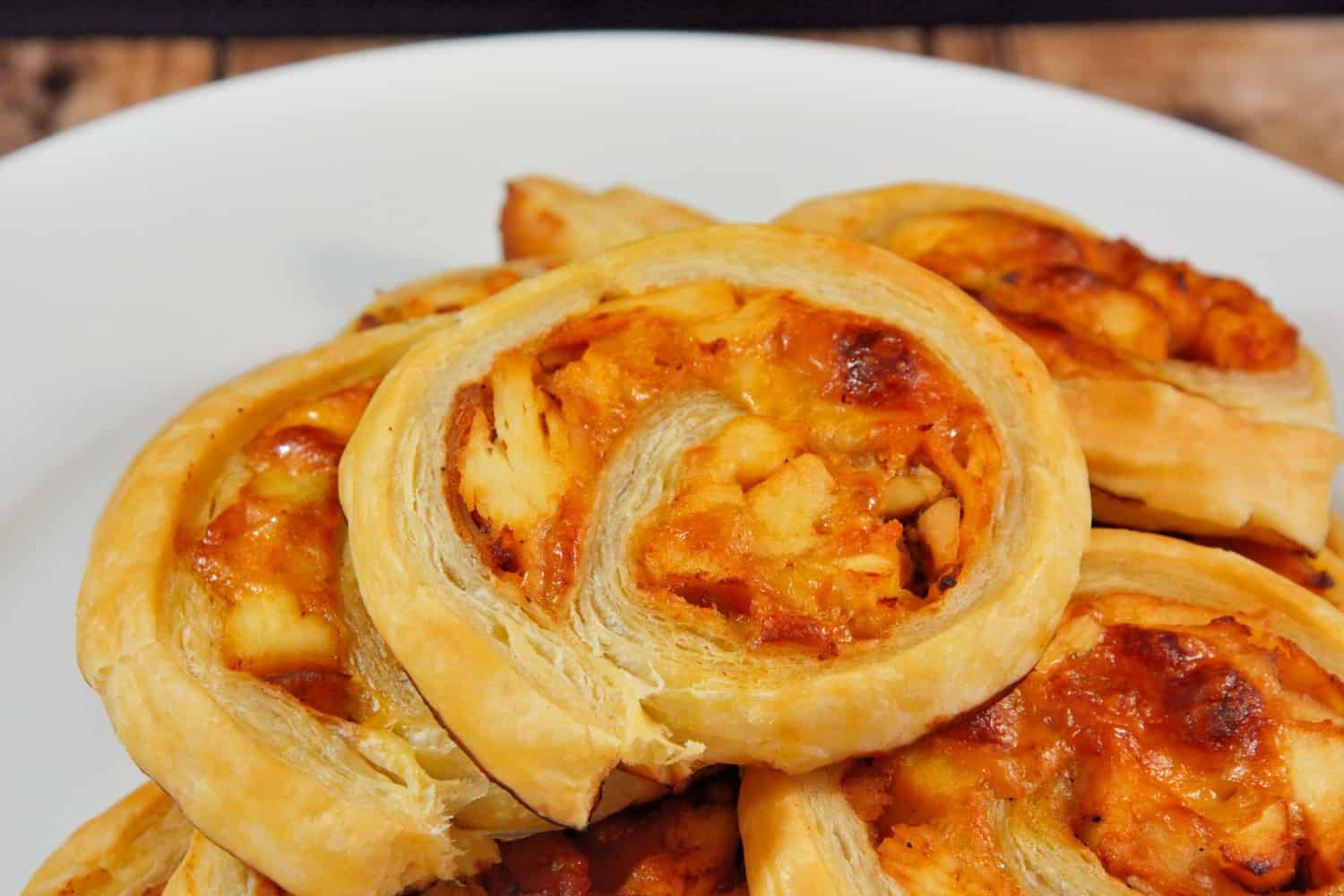 BBQ chicken pinwheels stacked on a white plate