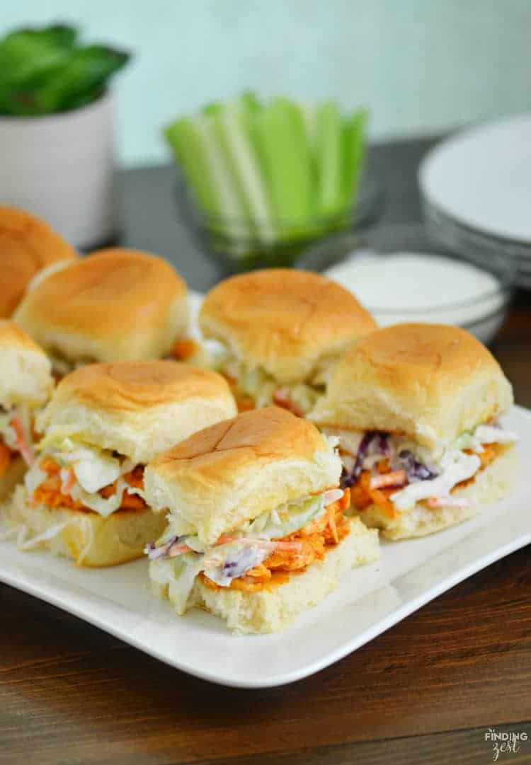 Buffalo chicken sliders on a white plate with celery in the background