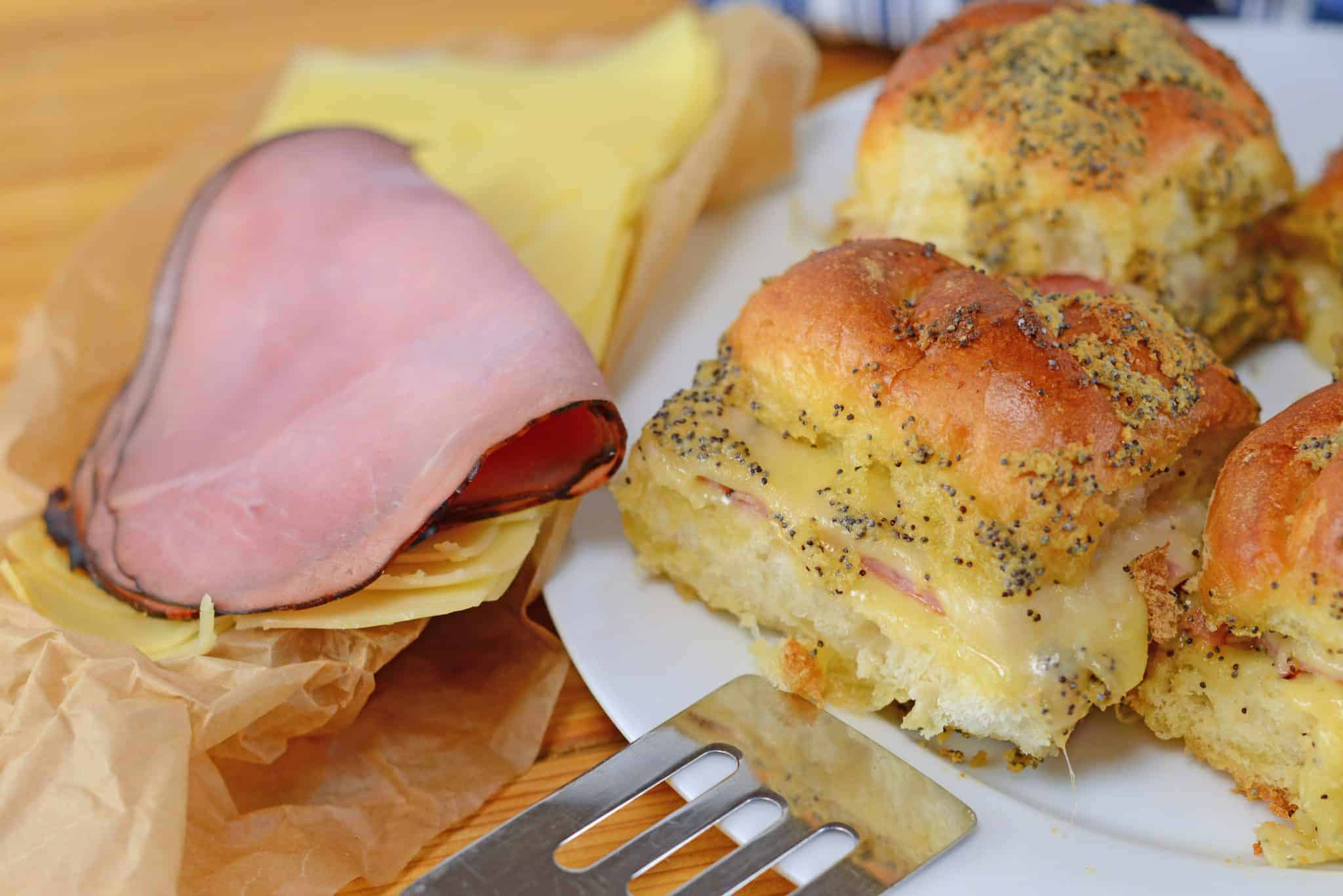 Ham and cheese sliders on a white plate with a spatula