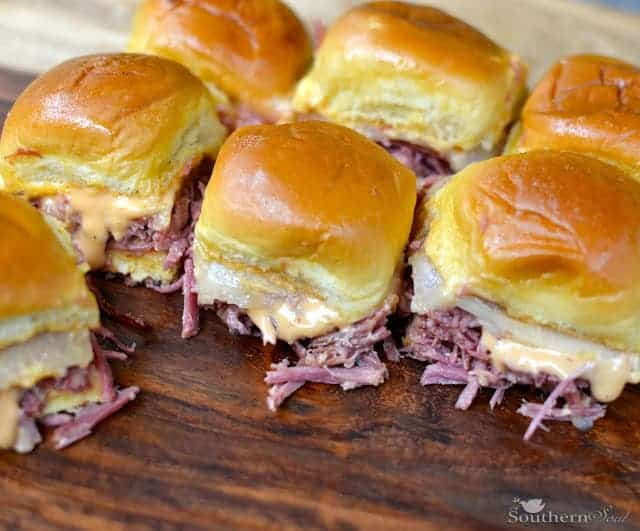 Reuben sliders on a wooden cutting board
