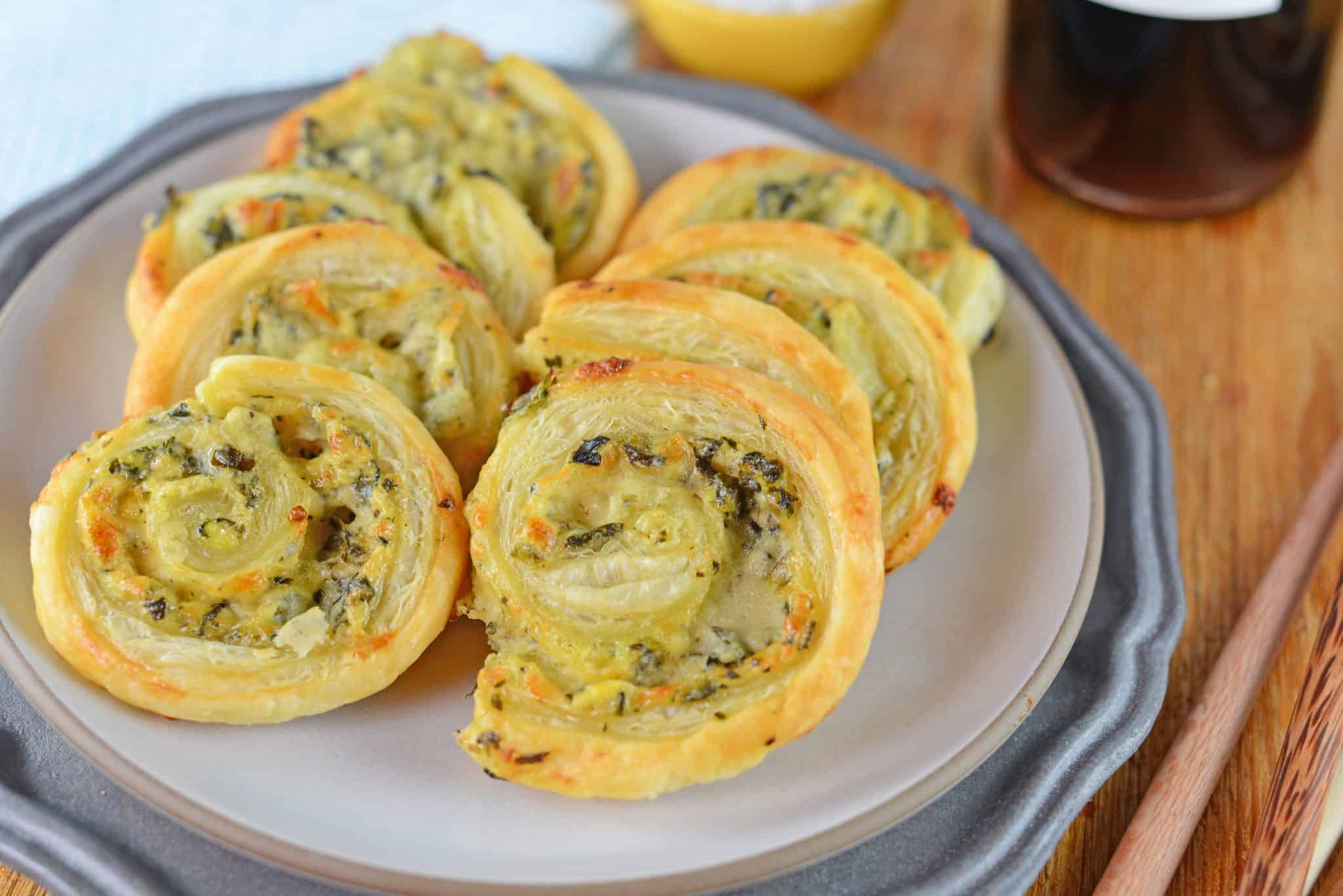 Spinach and artichoke pinwheel recipes stacked on a plate