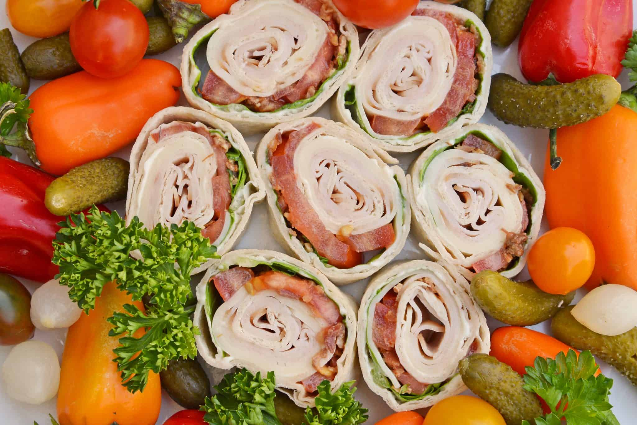 Turkey club pinwheel recipes with veggies on a tray