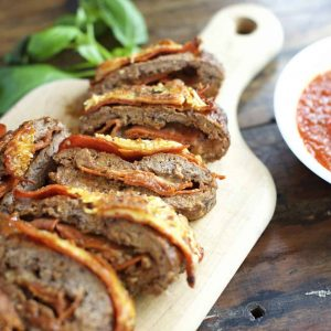 Pizza meatloaf cut into slices on a cutting board