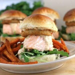 Cajun salmon slider sandwich recipes on a white plate with sweet potato fries