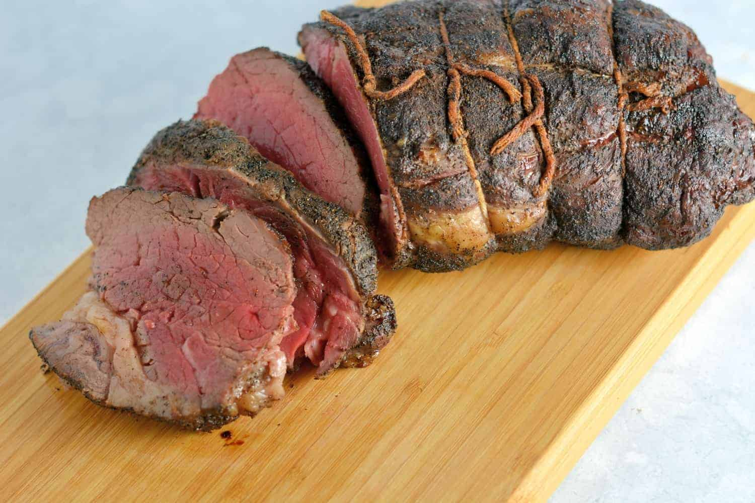 Coffee crusted tenderloin sliced on a cutting board - Christmas main dishes