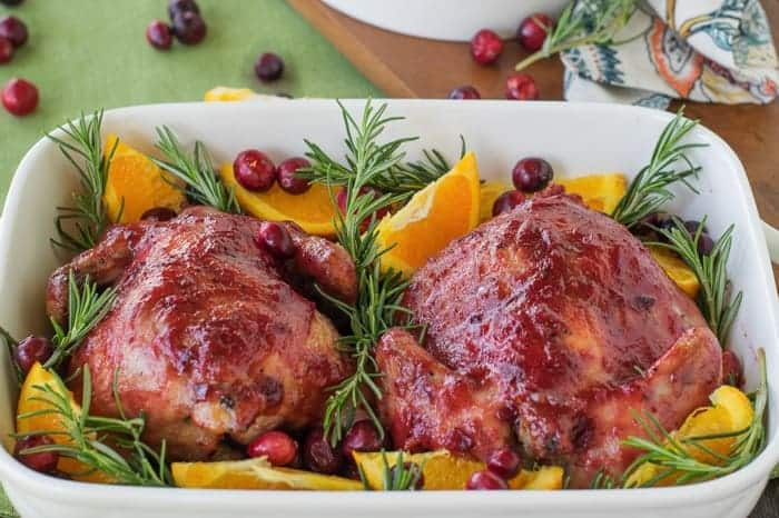 Cornish hens in a white dish with cranberries and oranges - Christmas main dishes