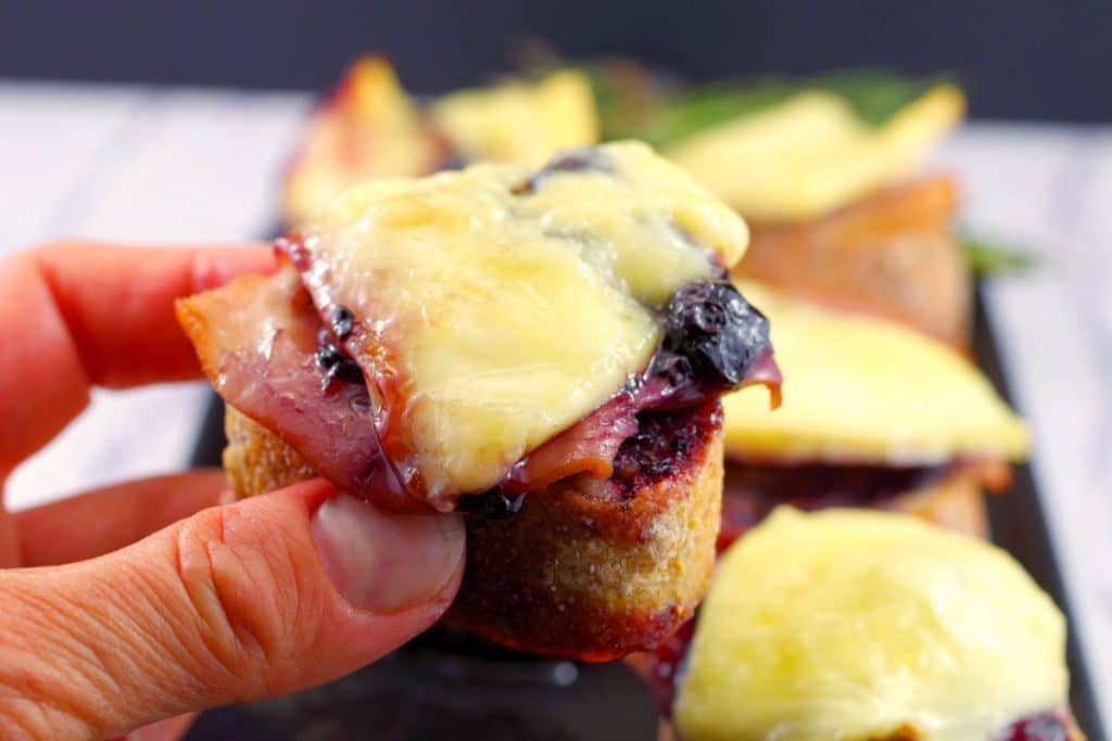 Brie turkey crostini in a hand, leftover turkey recipes