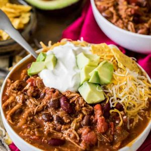 Turkey chili in a white bowl with sour cream and cheese - leftover turkey recipes