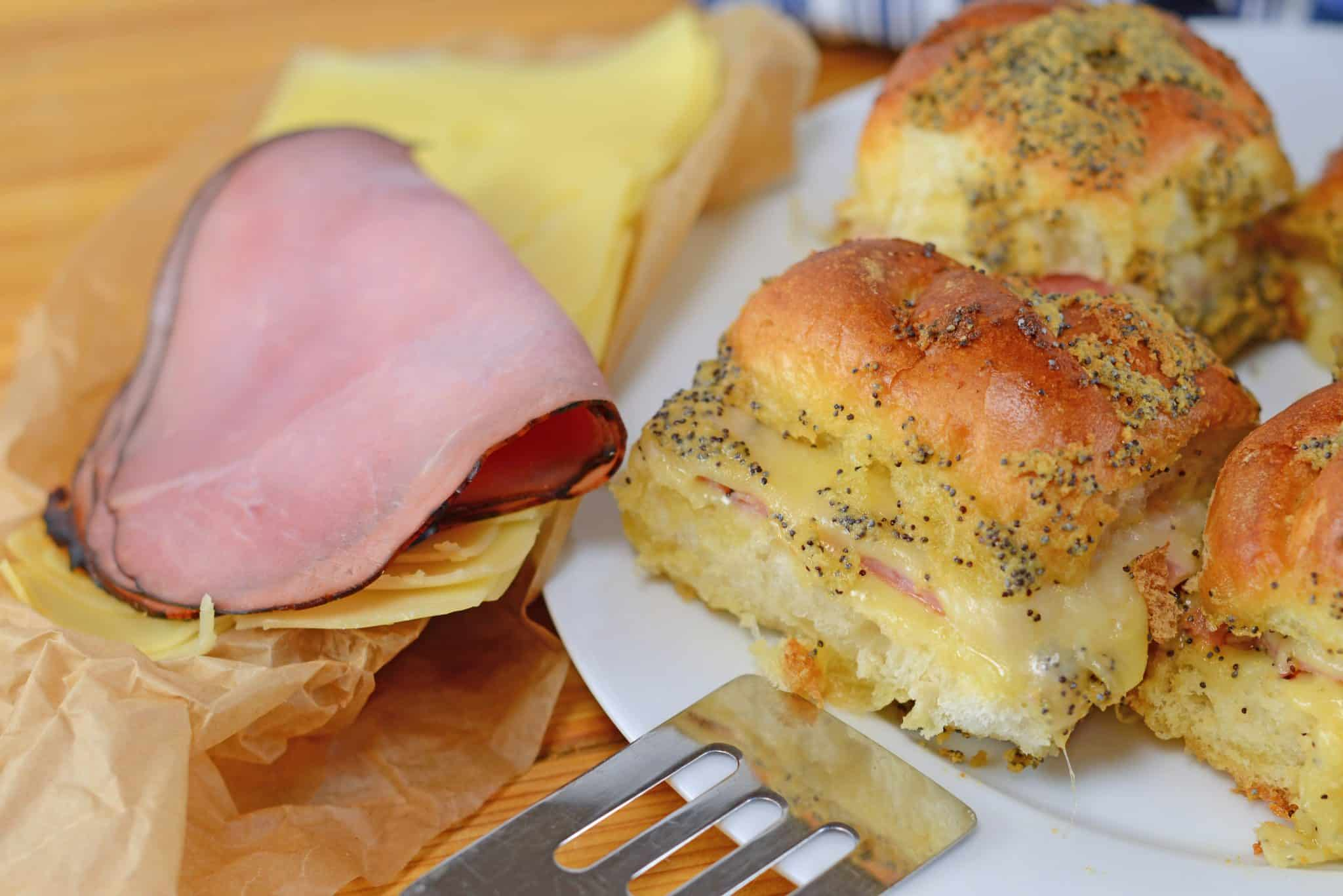 Ham and cheese slider sandwich recipes on a white dish with a spatula