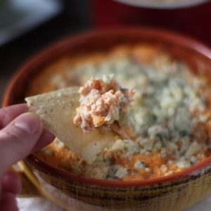 Buffalo turkey dip in a crock with a chip - leftover turkey recipes