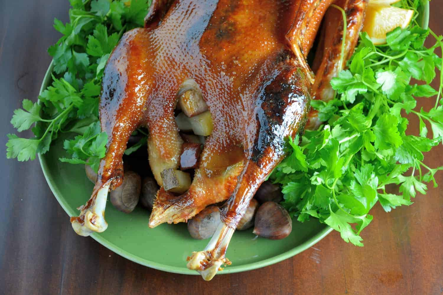 Roasted goose on a green plate with lettuce - Christmas main dishes