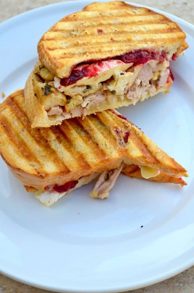 Thanksgiving panini cut in half on a white plate - leftover turkey recipes