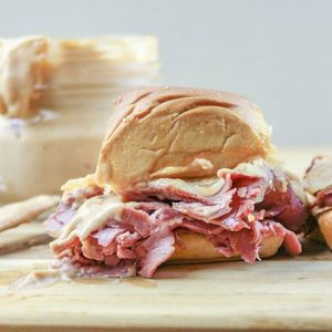 Corned beef slider sandwich recipes on a cutting board with sauce in the background