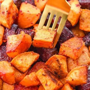 Thanksgiving sides close up of roasted beets and sweet potatoes on a fork