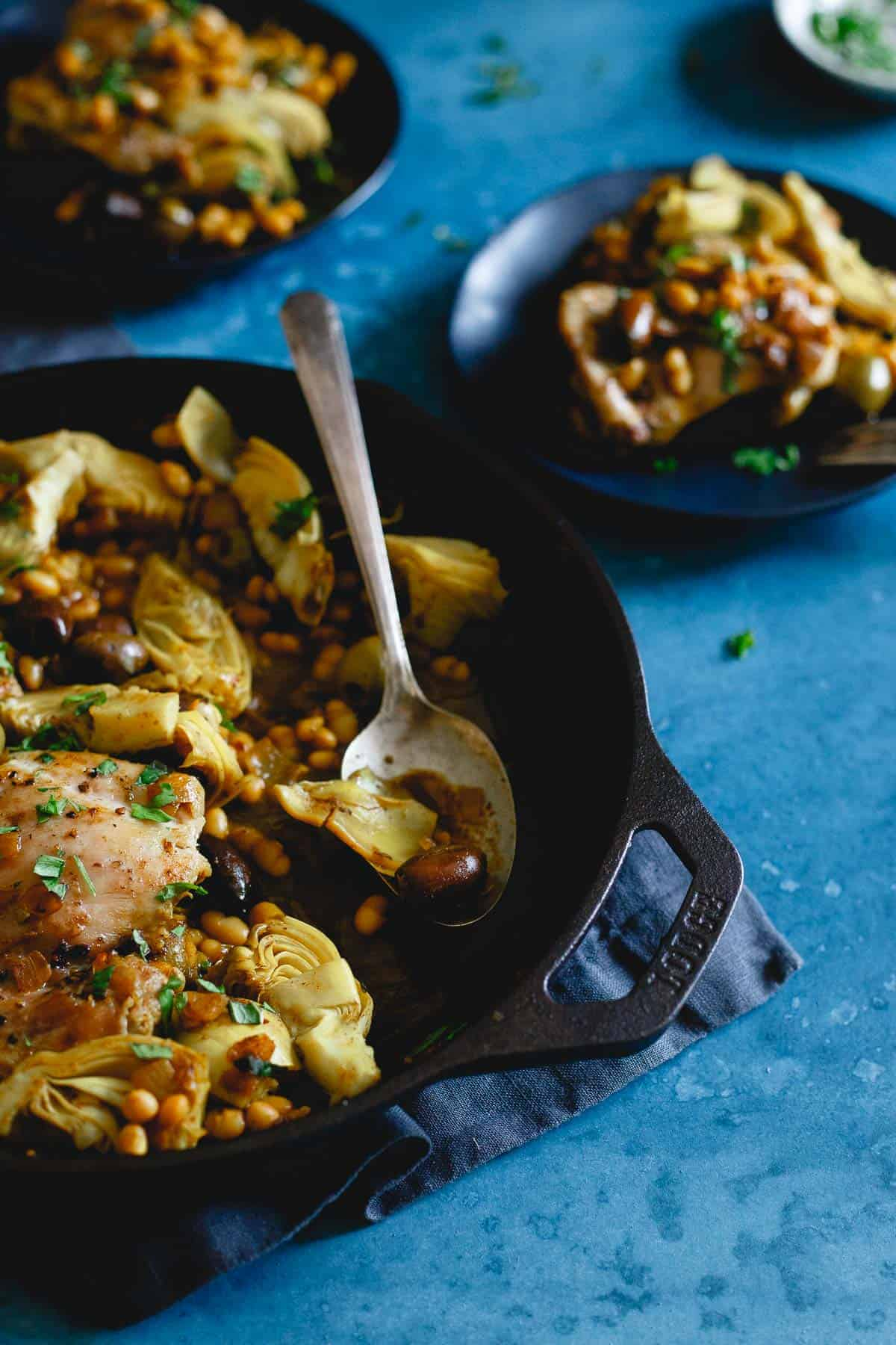Chicken artichoke and olives in a skillet with a spoon - skillet dinners