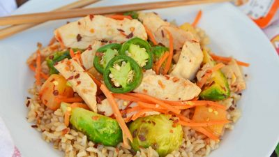 Quick Szechuan Chicken and Rice is an easy dinner recipe featuring chicken strips, brussels sprouts, carrots and pineapple over brown rice. All ready in 15 minutes! #quickchickendinners #szechuanchicken www.savoryexperiments.com