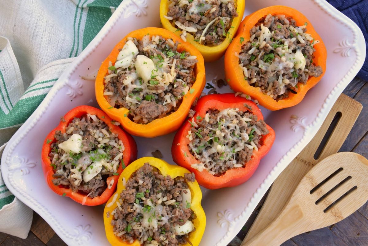 Classic Stuffed Peppers are bell peppers stuffed with ground beef, rice, cheese and spices. A timeless meal ready in 30 minutes and easily made ahead. #stuffedpeppers #stuffedbellpeppers www.savoryexperiments.com