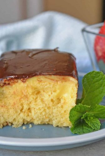 Boston Cream Poke Cake with Strawberries on a blue plate